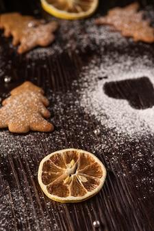 Lebkuchenplätzchen im weihnachtstannenbaum, puderzucker auf holztisch, winkelsicht, selektiver fokus auf zitrusfrucht trockneten zitrone