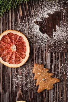 Lebkuchenplätzchen im weihnachtstannenbaum, puderzucker auf holztisch, zitrusfrucht trocknete pampelmuse, tannenbaumast, draufsicht