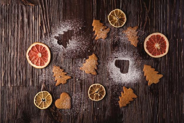 Lebkuchenplätzchen im weihnachtstannenbaum und im herzen formen, puderzucker auf holztisch, zitrusfruchttrockenfrüchte, draufsicht