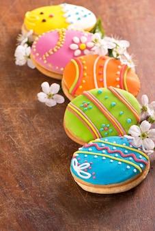 Lebkuchenplätzchen in der form von farbeiern auf dunklem hölzernem hintergrund. frohe osterkarte. helle kekse. leckereien für kinder. speicherplatz kopieren