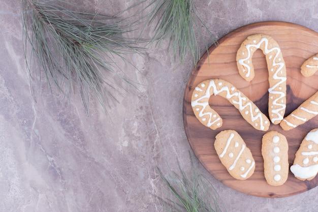 Lebkuchenplätzchen in oval- und stockform auf einem holzbrett