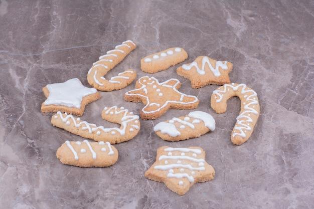 Lebkuchenplätzchen in stern-, stock- und ovalform auf marmor.