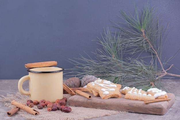 Lebkuchenplätzchen in stern- und ovalform mit zimt und einer tasse milch.