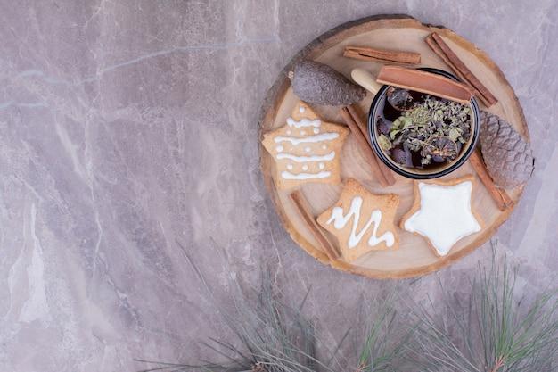 Lebkuchenplätzchen in sternform mit einer tasse kräutertee und zimt.