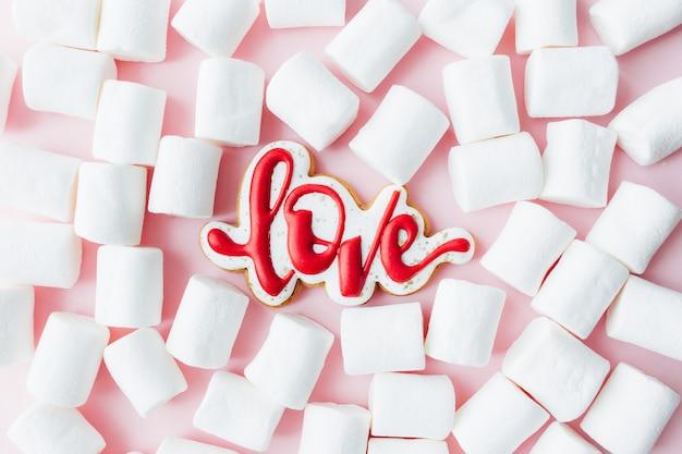 Lebkuchenplätzchen lieben mit weißem marshmallow. valentinskarte. rosa hintergrund. hochwertiges foto