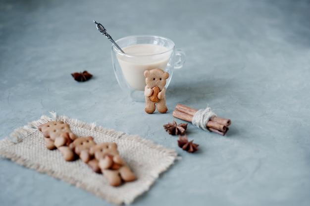 Lebkuchenplätzchen mit der form von den bären, die mandel mit zimtstangen und eierpunsch halten