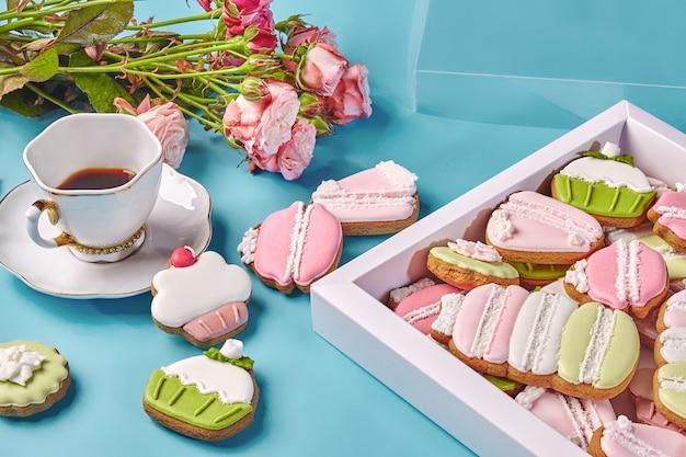 Lebkuchenplätzchen mit tasse kaffee und rosen auf blau