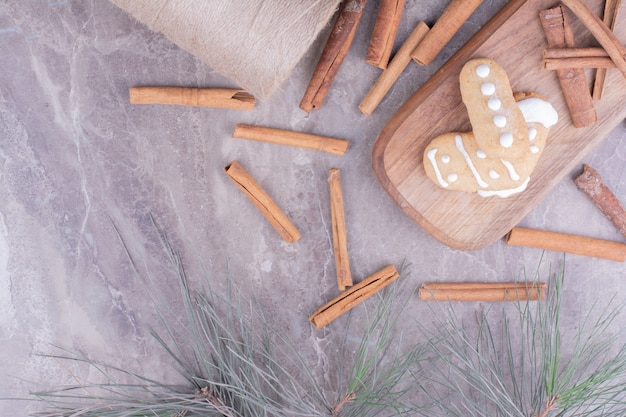Lebkuchenplätzchen mit zimtstangen auf langem holzbrett.