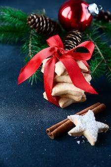 Lebkuchenplätzchen verziert mit einem roten band mit einer bogen- und weihnachtskugel