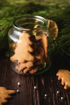 Lebkuchenplätzchen weihnachtstannenbaum und -herz formen im glänzenden glasgefäß auf holztisch, zitrusfrucht getrocknete zitrone, tannenbaumast, winkelsicht, selektiver fokus
