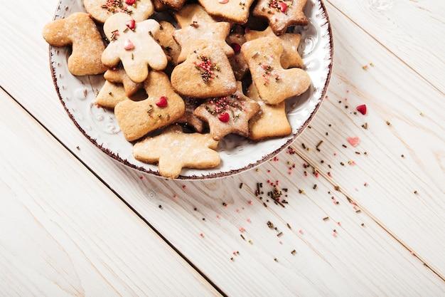 Lebkuchentellerweihnachtsfeiertag und neujahrskonzeptweißer holztisch