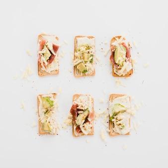 Lecker arrangierte toasts mit käse; avocado und speck auf weißem hintergrund
