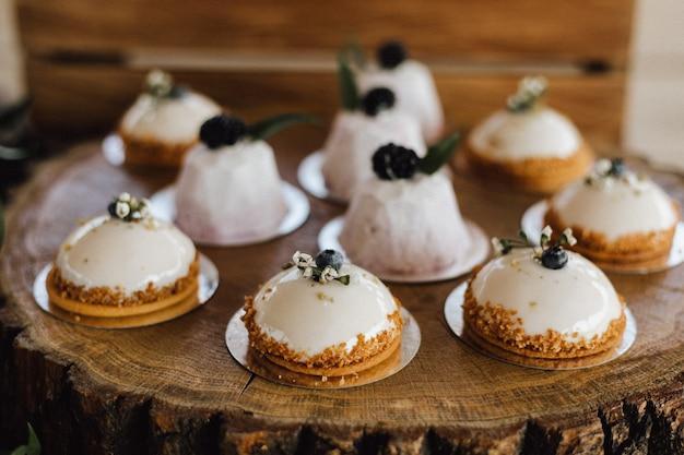 Lecker dekorierte cremige desserts auf dem holztablett