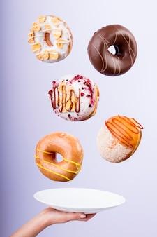 Lecker fliegende donuts mischung von aromen - weibliche hände, die einen teller halten