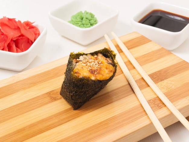 Lecker gebackener gunkan mit aal auf einem holzbrett