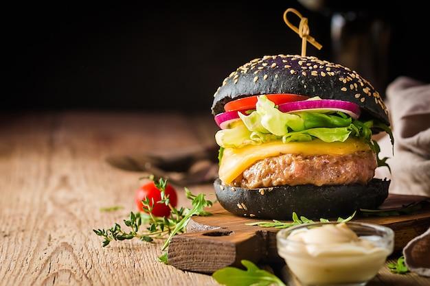 Lecker gegrillter klassischer schwarzer rindfleischburger mit salat und mayonnaise-sauce auf einem rustikalen holztisch mit kopierraum