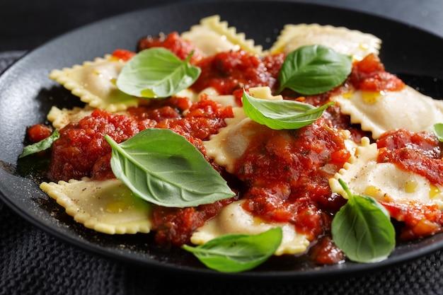 Lecker gekochte italienische ravioli mit tomatensauce und basilikum auf dunklem teller serviert.