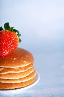 Leckere amerikanische pfannkuchen mit erdbeeren auf weißem teller gegen blauen hintergrund