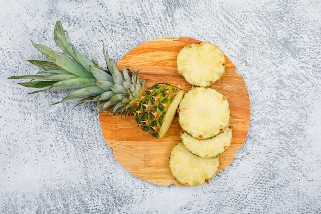 Leckere ananasscheiben in einem runden schneidebrett auf grunge-oberfläche, draufsicht.