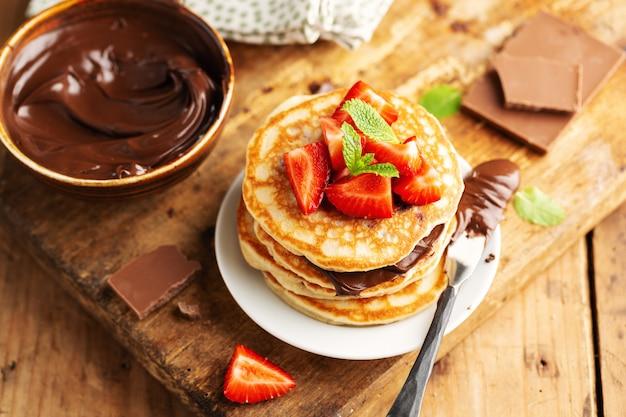 Leckere appetitliche, frisch zubereitete pfannkuchen mit erdbeer- und schokoladenpaste zum frühstück. nahansicht Premium Fotos