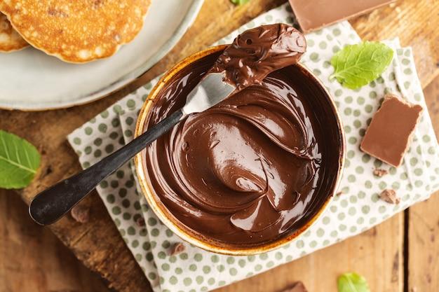 Leckere appetitliche, frisch zubereitete schokoladenpaste, die zum frühstück in einer schüssel serviert wird. nahansicht