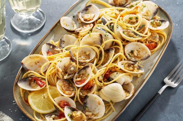 Leckere appetitliche frische hausgemachte muscheln alle vongole meeresfrüchteteigwaren mit knoblauch und weißwein auf teller. nahansicht.