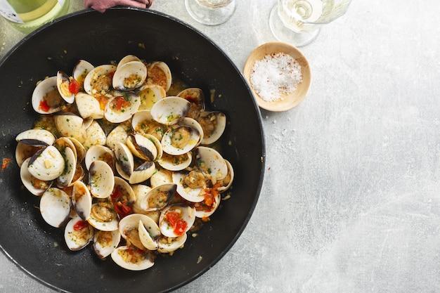 Leckere appetitliche frische hausgemachte muscheln alle vongole mit knoblauch und weißwein auf pfanne. draufsicht.