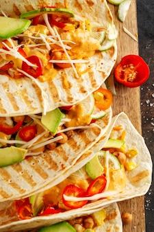 Leckere appetitliche frische hausgemachte vegane tacos mit kichererbsen und gemüse an bord serviert. draufsicht.