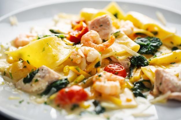 Leckere appetitliche nudeln mit garnelen, gemüse und spinat auf teller serviert.
