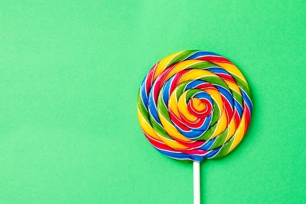 Leckere appetitliche party zubehör sweet swirl süßigkeiten lollypop auf grünem hintergrund draufsicht
