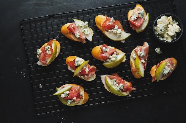 Leckere appetitliche vorspeisen kleine sandwiches mit schinken, birne, blauschimmelkäse an bord serviert. draufsicht.
