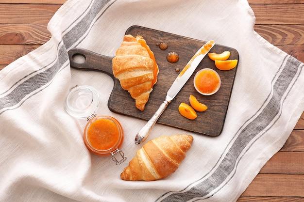 Leckere aprikosenmarmelade mit croissants auf dem tisch
