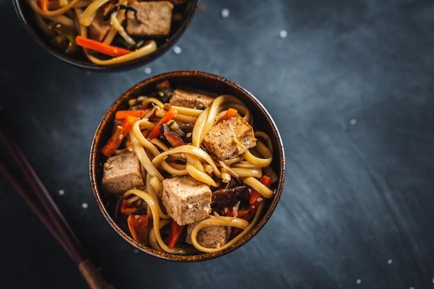 Leckere asiatische nudeln mit käsetofu und gemüse auf tellern.