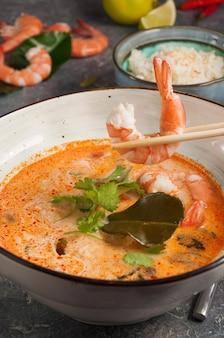 Leckere asiatische tom yam suppe ein mann hält eine garnele mit stäbchen