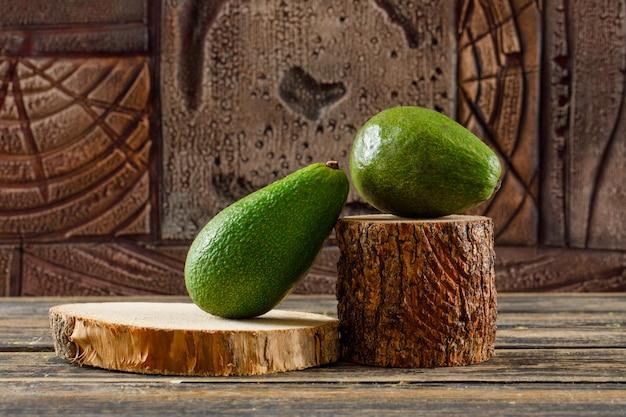 Leckere avocado in holzstücken auf einem holztisch