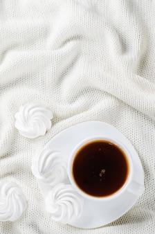 Leckere baiserplätzchen und eine tasse heißen tee.