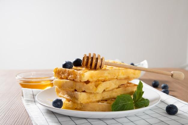 Leckere belgische waffeln auf einem teller mit honig und frischen blaubeeren