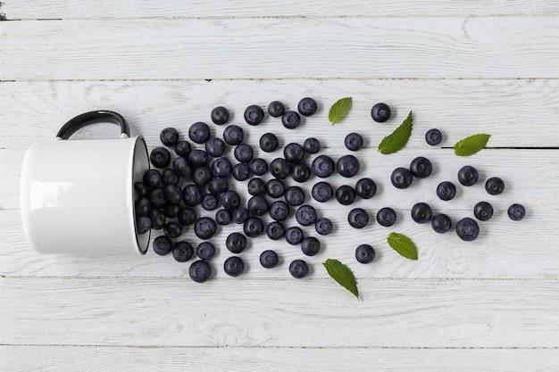 Leckere blaubeeren aus becher über holztisch verstreut, flach gelegen. saisonales vegetarisches essen
