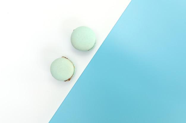 Leckere blaue französische macarons oder makronen auf einem weißen und blauen hintergrund.