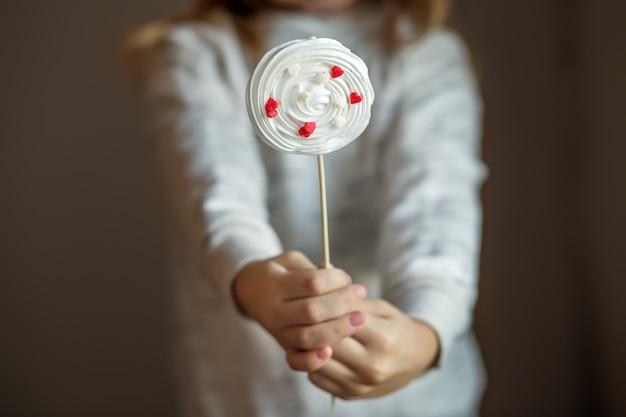 Leckere bonbons baiser in kinderhänden. das konzept von süßigkeiten, party, bäckerei.