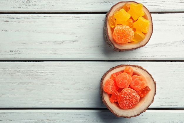Leckere bonbons in holzbechern auf dem tisch