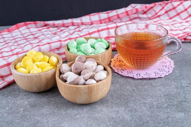 Leckere bonbons und eine tasse tee auf marmoroberfläche