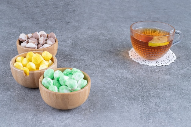 Leckere bonbons und eine tasse tee mit zitronenscheibe auf marmoroberfläche