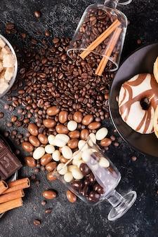 Leckere bonbons und süßigkeiten auf einem dunklen holzbrett. studiofoto. ansicht von oben
