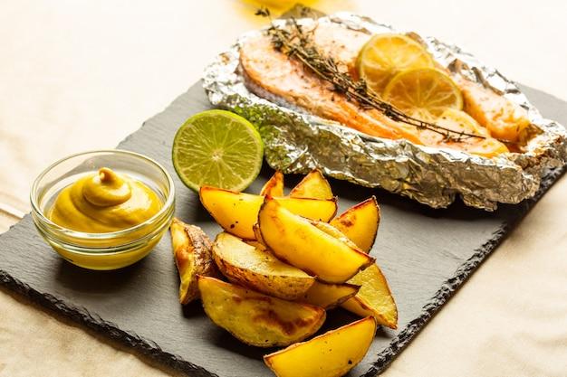 Leckere bratkartoffeln und senf auf der schwarzen schieferoberfläche mit gebackenem fisch