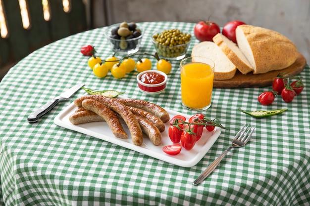 Leckere bratwurst mit tomatensaft, maisbrot und oliven auf dem tisch serviert