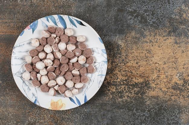Leckere braune bonbons auf buntem teller.
