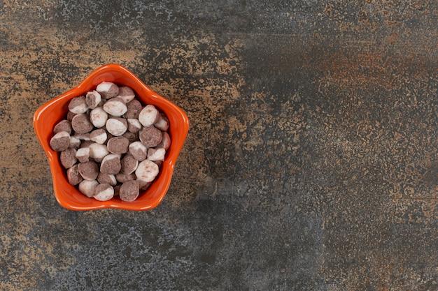 Leckere braune bonbons in der orangefarbenen schüssel.
