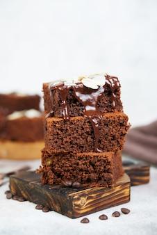 Leckere brownie-schokoladenkuchen mit warmer schokolade übergossen und mit mandelblättern dekoriert. vertikale ausrichtung
