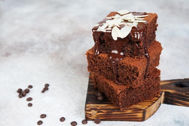 Leckere brownie-schokoladenkuchen mit warmer schokolade übergossen und mit mandelblättern dekoriert.